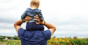 Baby auf Schultern seines Vaters sitzend