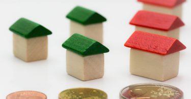 Betriebskosten Nebenkosten als Münzen verteilt vor Miniaturhäusern