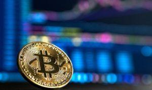 Bitcoin vor Bildschirm mit Statistiken