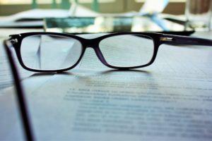 Brille auf Unterlagen für Schuldnerberatung