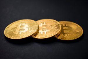 Drei goldene Bitcoins auf schwarzem Untergrund