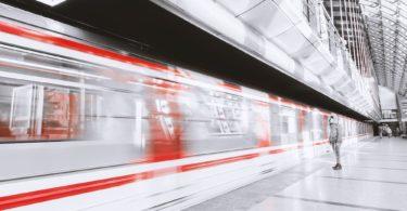 Durchfahrt eines Zuges und wartender Reisender mit DB Sparpreis Ticket