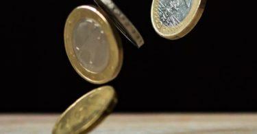 Fallende Euromünzen vor schwarzem Hintergrund für Kreditvergleich