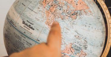 Finger deutet auf alten Globus für nächste Reise mit Reiseversicherung