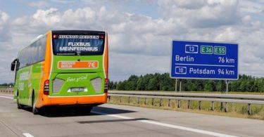 Flixbus Fernbus auf Autobahn und Autobahnschild mit Entfernungsangabe nach Berlin