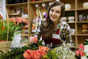 Floristin mit Berufsunfähigkeitsversicherung sortiert Blumen