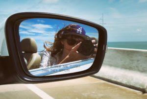 Frau macht Foto von sich in Seitenspiegel von Mietwagen