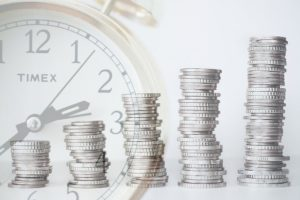 Fünf größer werdende Münzstapel mit Uhr im Hintergrund für steigenden Wert beim Lebensversicherung kündigen