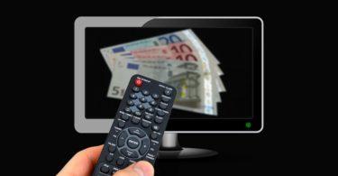 Geld für Rundfunkbeitrag auf Bildschirm und Hand die Fernbedienung hält