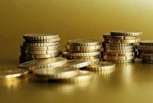 Gestapeltes Kleingeld für Kredit umschulden auf goldenem Untergrund