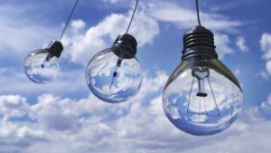 Glühbirnen mit Ökostrom betrieben vor blauem Himmel