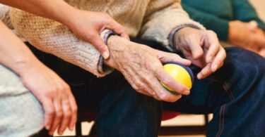 Hände einer Pflegerin und Hände eines Rentners mit Pflegezusatzversicherung der einen Ball hält
