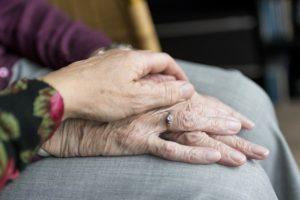 Hand auf Händen von Seniorin mit Pflegezusatzversicherung