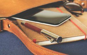 Handy mit Handyversicherung in Tasche mit Notizbuch und Stift