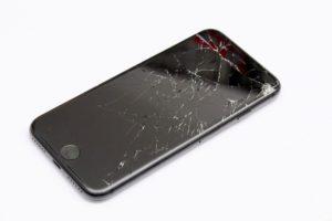 Handy mit Handyversicherung und gebrochenem Display auf weißem Untergrund