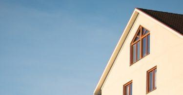 Beiges Haus mit Gebäudeversicherung vor blauem Himmel