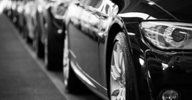 Hintereinander parkende schwarze Autos mit Kfz Versicherung