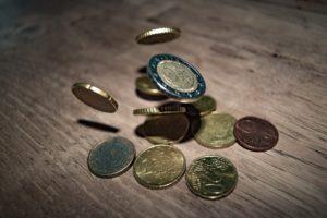 Kleingeld für Gemeinschaftskonto fällt auf Holzboden