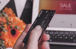 Kreditkarte in Hand vor Laptop gehalten