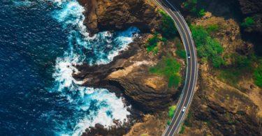 Luftaufnahme von Mietwagen auf Küstenstraße fahrend