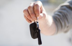Mann hält Mietwagen Schlüssel