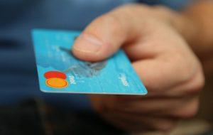 Mann hält mit einer Hand Studentenkreditkarte hin