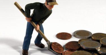 Miniaturfigur schaufelt Kleingeld für Bausparvertrag mit Schaufel zur Seite