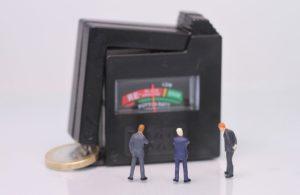 Miniaturfiguren blicken auf Barometer mit Wertrückgang Kapitallebensversicherung
