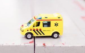 Spielzeugkrankenwagen auf weißem Holztisch