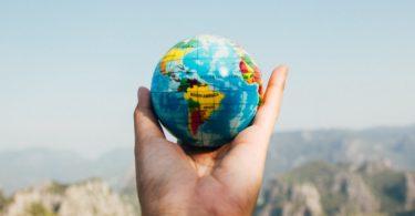 Miniglobus in Hand vor Himmel gehalten als Sinnbild für Auslandskrankenversicherung
