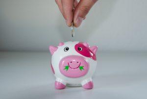 Münze wird in rosa Sparschwein geworfen