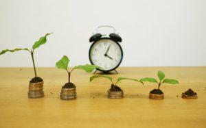 Fünf Münzstapel für Kredit umschulden mit Uhr im Hintergrund