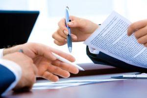 Nahaufnahme Vertragsdokumente Girokonto und Hände zweier Personen