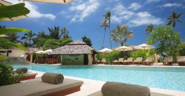 Pauschalreise Hotelpool mit Liegen und Sonnenschirmen unter blauem Himmel