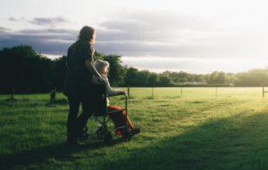 Pfleger über Pflegezusatzversicherung schiebt Frau in Rollstuhl