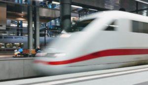 Reisende mit Bahntickets und ein einfahrender ICE der Deutschen Bahn in einem Bahnhof
