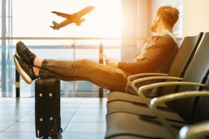 Reisender mit Auslandskrankenversicherung mit den Füßen auf Koffer hochgelegt am Flughafen sitzend