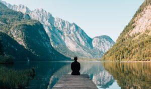 Reisender mit Auslandskrankenversicherung blickt in die Ferne während er auf Steg eines Bergsees sitzt