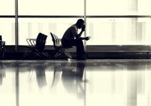 Reisender sitzt im Flughafen und prüft Fluggastrechte auf Smartphone