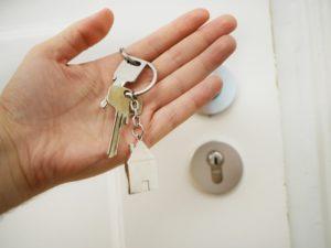 Schlüssel mit Schlüsselversicherung in Hand gehalten vor Wohnungstür