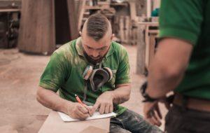 Schreiner mit Berufsunfähigkeitsversicherung macht Notizen