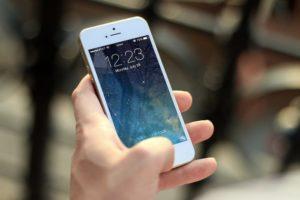 Smartphone mit Handyversicherung in Hand gehalten