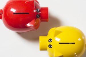 Rotes und gelbes Sparschwein für Kredit umschulden