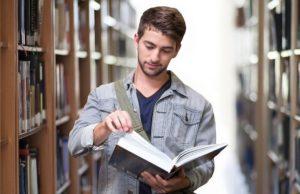 Student blättert durch Buch in der Bibliothek