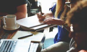 Studenten arbeiten an Laptop und Notizbuch