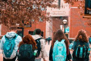 Fünf Studenten mit Studentenkonto gehen Richtung Universität