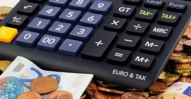 Taschenrechner und Geld um Höhe der Versicherungssteuer zu berechnen