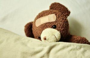 Teddybär halb zugedeckt mit weißer Decke als Sinnbild für Familienversicherungsschutz über Arbeitgeberzuschuss Private Krankenversicherung
