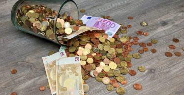 Umgefallenes Glas aus dem Kleingeld und Geldscheine für Umschuldung fallen