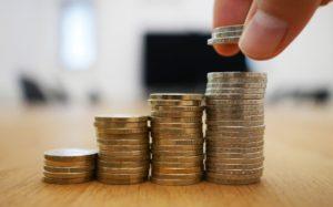 Vier Münzstapel auf welche weitere Münzen gelegt werden als Betriebliche Altersvorsorge